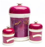 Sale 9054E - Lot 38 - A group of three Victorian fuschia coloured ceramic storage jars and lids, th largest bearing remnants of a painted and gilt label.