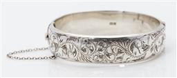 Sale 9123J - Lot 334 - An English hallmarked sterling silver bangle, Birmingham 1963, the upper half hand engraved with scrolling foliates and fitted with ...