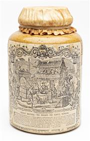 Sale 9054E - Lot 45 - A Huntley and Palmer earthenware tea canister with two paper labels, one for PH Benn, wholesaler and opposing pictorial label for C...