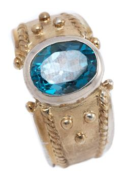 Sale 9253J - Lot 324 - A SILVER GILT TOPAZ RING; rub set in silver with an oval cut London blue topaz to bead design, width 11.5mm, size L, wt. 8.10g.