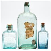 Sale 9054E - Lot 50 - Three glass bottles in blue and green  each with impressed details to include Rowes Patent Farmer;s Friend, Skabcura Dip Co Chicago I.