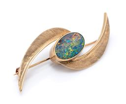Sale 9221 - Lot 334 - A VINTAGE 9CT GOLD OPAL BROOCH; collet set with an oval opal triplet (hairline) to textured leaves, size 55 x 20mm, wt.5.03g.
