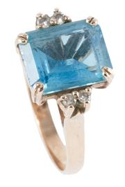 Sale 8974 - Lot 311 - A 9CT GOLD TOPAZ AND DIAMOND RING; set with an emerald cut blue topaz of approx. 3.00ct (chipped), between shoulders set with 4 roun...