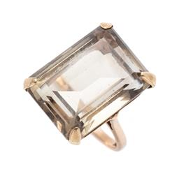 Sale 9260H - Lot 307 - A 9ct gold smoky quartz cocktail ring; claw set with an emerald cut smoky quartz of approx. 21.44ct, top size 21 x 16mm, size P, wt....