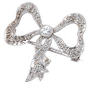 Sale 8965 - Lot 399 - AN EDWARDIAN STYLE DIAMOND BOW BROOCH; centre collet set with a round brilliant cut diamond of approx. 0.09ct to ribbon surround set...