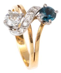 Sale 9124 - Lot 415 - AN 18CT GOLD SAPPHIRE AND DIAMOND RING; claw set with an Old European cut diamond of approx. 0.38ct, P1, opposite a round cut blue s...