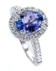 Sale 8899 - Lot 372 - A TANZANITE AND DIAMOND CLUSTER RING; set in 18ct white gold with an approx. 1.50ct tanzanite to surround and upswept shoulders set...