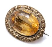 Sale 8999 - Lot 333 - AN ANTIQUE GOLD CASED CITRINE BROOCH; oval cut citrine of approx. 11.65ct to engraved surround, size 25 x 20mm.