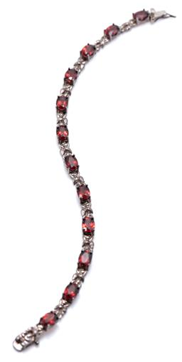 Sale 9169 - Lot 348 - A SILVER GARNET BRACELET; set with 12 oval cut brown garnets totalling approx. 10ct, to a box clasp with safety clip, length 19cm, w...