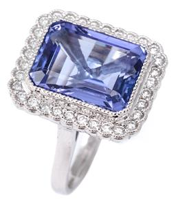 Sale 9124 - Lot 388 - A TANZANITE AND DIAMOND COCKTAIL RING; featuring an emerald cut tanzanite of approx. 6.84ct to scalloped surround of 32 round brilli...