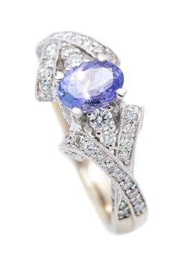 Sale 9260H - Lot 390 - An 18ct white gold tanzanite and diamond ring; centring an oval cut tanzanite (chipped), adjacent to 4 round brilliant cut diamonds...
