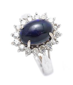 Sale 9260H - Lot 394 - A 14ct white gold opal and diamond cluster ring; centring a cabochon solid opal with violet and green flashes (scratches) to surroun...