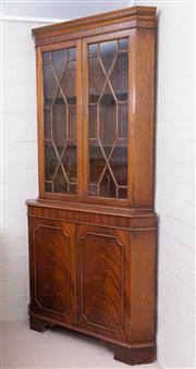 Sale 8550H - Lot 141 - An English mahogany vintage Georgian style corner cabinet, the shaped cornice on twin quarrelled doors enclosing shelving, the cupbo...