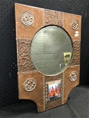 Sale 9048A - Lot 52 - An arts & crafts hand hammered and rivetted copper mirror of square form with curved lower corners flanking an enamelled panel depic...