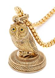 Sale 9083 - Lot 572 - A GILT FOB SEAL NECKLACE; 75cm belcher chain with parrot clasp attached with a 45mm fob seal featuring an owl perched on a 27.6mm ba...