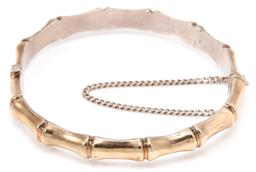 Sale 9145 - Lot 383 - A VINTAGE 9CT GOLD SILVER LINED BAMBOO BANGLE; 7mm wide hinged hollow bangle to box clasp with safety chain, made in New Zealand, in...