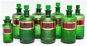 Sale 9054E - Lot 71 - Seven large and one small green glass ribbed bottles bearing painted pharmacological labels for various tinctures including Arnica a...