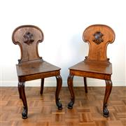 Sale 8000 - Lot 133 - A pair of Victorian carved oak hall chairs with applied shields and cabriole legs.