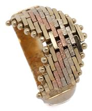 Sale 9046 - Lot 563 - A THREE TONE 14CT GOLD RING; chevron shape gate link style top in yellow white and rose gold, size K, top width 8mm, wt. 4.95g.