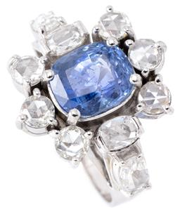 Sale 9140 - Lot 388 - AN 18CT WHITE GOLD SAPPHIRE AND DIAMOND COCKTAIL RING; centring an approx. 4.20ct blue oval cushion cut Ceylon sapphire (abraded fac...