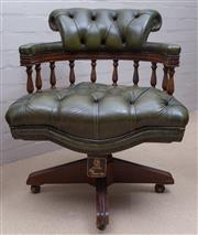 Sale 8550H - Lot 137 - A vintage deep buttoned green leather upholstered swiveling desk chair, the collar back on spindle on arcaded spindle arms above th...