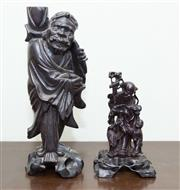 Sale 8368A - Lot 58 - A pair of Oriental timber carvings, including a robed traveller and an elder and child with a stork and flowers, taller H 30cm