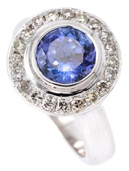 Sale 9140 - Lot 392 - AN 18CT WHITE GOLD TANZANITE AND DIAMOND RING; target cluster rub set with a round cut tanzanite of approx. 2.50ct encircled by 20 r...