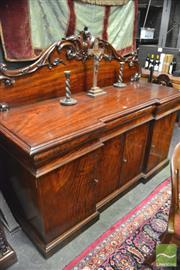 Sale 8359 - Lot 1011 - Unusual Early Victorian Mahogany Breakfront Sideboard, with carved back, three shaped drawers & four frameless doors showing full ve...