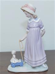 Sale 8368A - Lot 62 - A Lladro figure of a young girl pulling a doll in a cart, H 28 cm