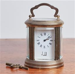 Sale 9099 - Lot 11 - A miniature carriage clock in a brass case by Dunhill. With key, Height 10cm