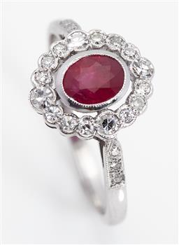 Sale 9123J - Lot 143 - An 18ct white gold ring, the oval cut ruby within a frame of 4 diamonds each spaced by 3 slightly smaller diamonds, a further 3 diam...