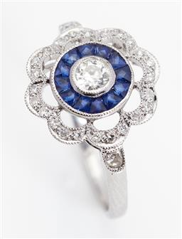 Sale 9123J - Lot 144 - An 18ct white gold ring, the centre round old cut diamond framed by a continuous band of 12 calibre cut sapphires within a looped fr...
