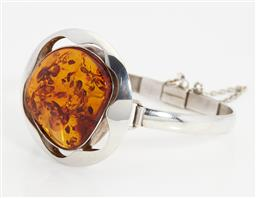 Sale 9123J - Lot 147 - A large sterling silver bangle, the large piece of amber in a stylised flower form frame, the bangle fitted with a box clasp and saf...