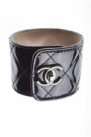 Sale 8315 - Lot 315 - ACHANEL QUILTED PATENT LEATHER BRACELET; stamped CHANEL B12 P. Made in Italy, M, with carry bag.