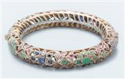 Sale 9037F - Lot 45 - AN INDIAN SILVER PLATED GEMSET SET HINGED BANGLE; 11mm round pierced design set with faceted sapphires, emeralds and rubies, interna...
