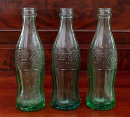 Sale 9190H - Lot 456 - A set of three coca cola bottles, Height 20cm