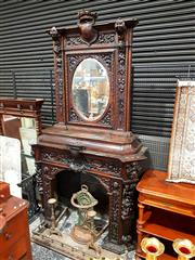 Sale 8693 - Lot 1042 - Victorian Oak Baronial Style Fireplace Surround, with oval mirror in a highly carved floral frame, with mask heads and fantastic arm...
