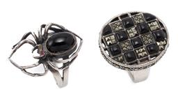 Sale 9186 - Lot 331 - TWO SILVER ONYX RINGS; an oval top set with cabochon onyx and round and carre cut marcasites to gallery set with further marcasites,...