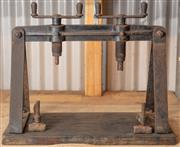 Sale 8984H - Lot 399 - A cast iron double handled triform press on timber base. Width 66cm