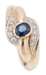 Sale 9083 - Lot 564 - A 9CT GOLD SAPPHIRE AND DIAMOND RING; bypass design centring a blue oval cut sapphire adjacent to 10 round brilliant cut shoulder di...