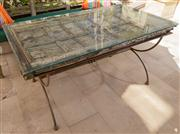 Sale 8595A - Lot 77 - An Indian carved door utilised as a table top on a forged iron base with glass top, H 76 x156 x 88cm