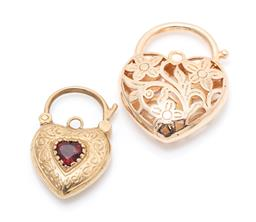 Sale 9260H - Lot 304 - Two heart shape padlock clasps; one in 9ct set with a heart cut garnet, size 28 x 18mm, wt. 6.23g, other gold plated with pierced fl...