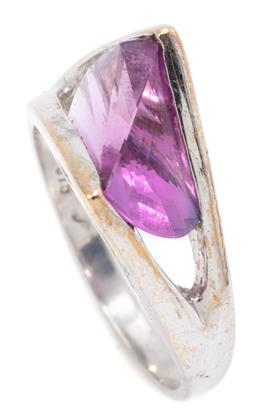 Sale 9156J - Lot 536 - A 9CT WHITE GOLD STONE SET RING; abstract design set with a fancy cut purple synthetic stone, size L, width 9mm, wt. 3.29g.