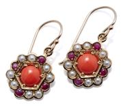 Sale 9037 - Lot 365 - A PAIR OF 9CT GOLD GEMSET EARRINGS; 11mm wide discs each centring a cabochon coral surrounded by 4 rubies and 8 seed pearls on a she...