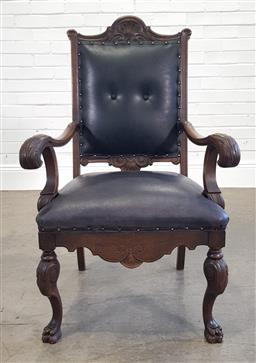 Sale 9215 - Lot 1077 - Early 20th Century Carved Oak Armchair, upholstered in buttoned dark probably black leather & raised on cabriole legs with paw feet...