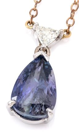 Sale 9132 - Lot 481 - A TANZANITE AND DIAMOND PENDANT NECKLACE; 18ct white gold pendant V claw set with a pear cut tanzanite of approx. 5.40ct surmounted...
