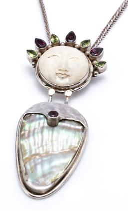 Sale 9194 - Lot 326 - A SHANO JEWELRY MAN IN THE MOON IVORY AND STONE SET PENDANT NECKLACE; carved mammoth ivory face with headdress of pear cut peridots...