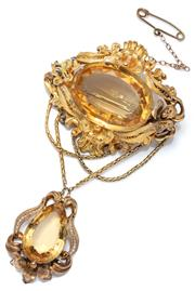 Sale 9046 - Lot 394 - AN ELEGANT ANTIQUE 18CT GOLD GEM SET STOMACHER BROOCH; centring an oval citrine of approx. 38.5ct within a cannetille floral and scr...