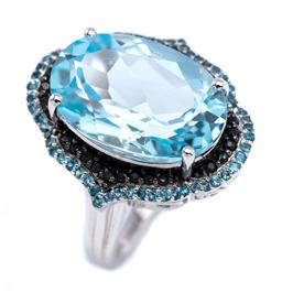 Sale 9194 - Lot 332 - A SILVER TOPAZ AND STONE SET COCKTAIL RING; featuring an oval cut blue topaz of approx. 13.40ct to double surround of black round cu...