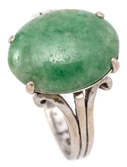 Sale 9132 - Lot 321 - A VINTAGE 14CT WHITE GOLD JADE RING; centring a 15 x 11.3mm oval green jade to split scroll shoulders, size P, wt. 4.71g.